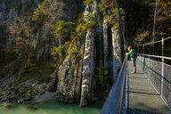 Austria, Tyrol, hiker on suspension bridge looking at Tiroler Ache in autumn - LBF02255