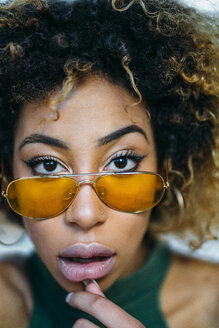 Portrait of young woman wearing yellow sunglasses - JCMF00007