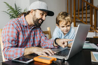 Father and son using laptop together - JRFF01999