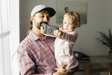Father holding his little daughter on his arm, playing with his smartphone - JRFF02005