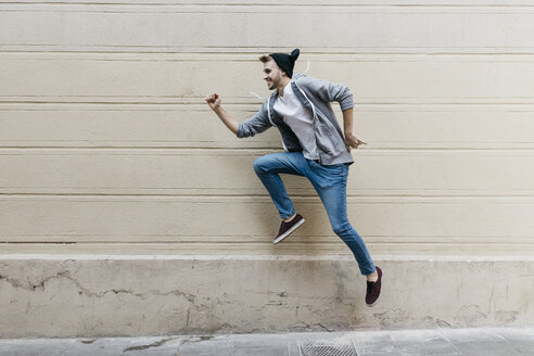 Happy young man jumping in front of a wall - JRFF02035