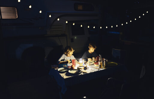 Brazil, Bonito, two boys drawing at camper in the dark - SSCF00010