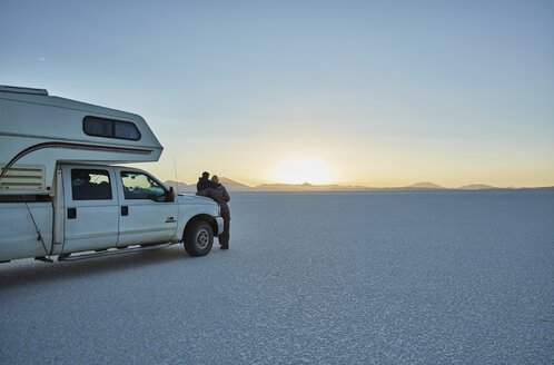 Bolivia, Salar de Uyuni, mother and son at camper on salt lake at sunset - SSCF00022