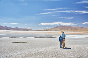 Bolivia, Laguna Colorada, mother and son at lakeshore with view to the Andes - SSCF00034