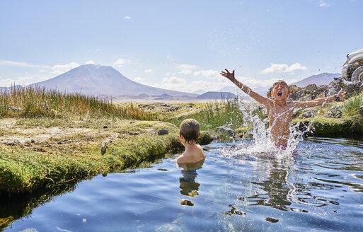 Chile, Salar del Carmen, two boys bathing in hot spring - SSCF00037