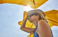Smiling woman wearing straw hat under sunsahde in sunlight - SSCF00055