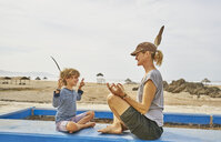 Chile, Arica, happy mother in yoga pose sitting with son on wall on the beach - SSCF00064