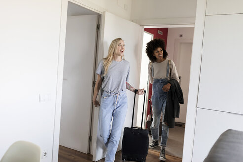 Two happy women with baggage arriving in accomodation - VABF01710
