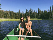 Shirtless brothers sitting in boat on Rucker Lake during sunny day at forest - CAVF55880