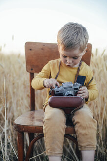 Curious boy adjusting vintage camera while sitting on chair amidst wheat field - CAVF55913