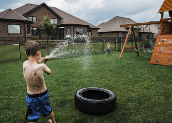 Rear view of shirtless boy spraying water on brother with garden hose at park - CAVF55928