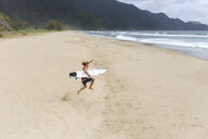 High angle view of shirtless man with surfboard jumping at beach - CAVF55934