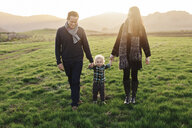 Smiling parents walking with son on grassy field against sky - CAVF55943