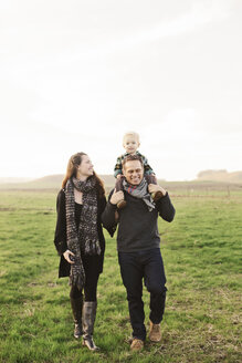 Father carrying son on shoulders while walking with wife on grassy field against sky - CAVF55946