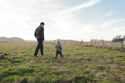 Rear view of father with son walking on grassy field against sky - CAVF55949