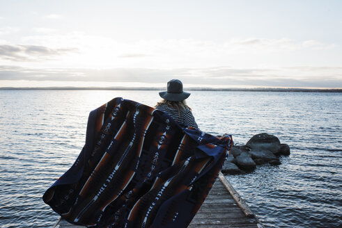 Rear view of woman with blanket standing on pier by Lake Simcoe against sky - CAVF55976