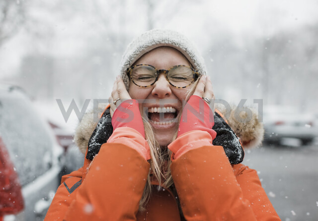 Happy woman with hands on chin screaming while standing on road during snowfall - CAVF55979