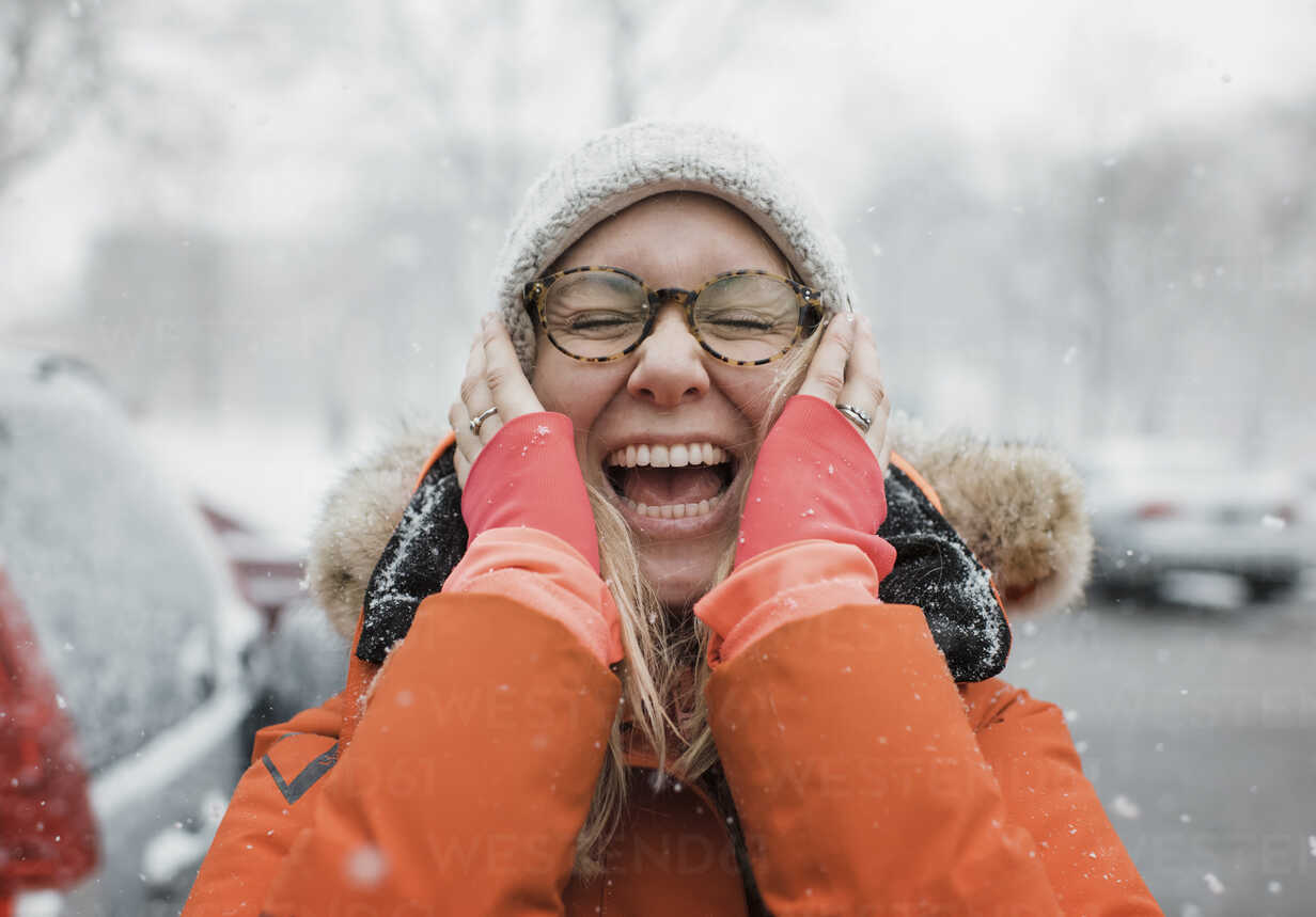 Happy woman with hands on chin screaming while standing on road during snowfall - CAVF55979 - Cavan Images/Westend61