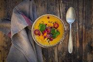 Bowl of curry dish with Hokkaido pumpkin, broccoli, tomatoes, pomegranate seed and black sesame - LVF07559