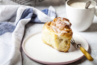 Home-baked cinnamon bun with icing sugar and a cup of coffee - SBDF03850