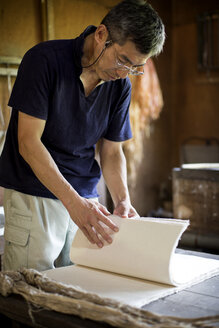 Japanese man standing in a workshop,  checking through sheets of traditional Washi paper. - MINF09602
