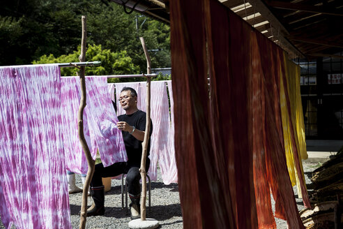 Japanese man sitting outside a textile plant dye workshop, hanging up freshly dyed pink fabric. - MINF09605
