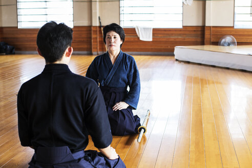 Female and male Japanese Kendo fighters kneeling opposite each other on wooden floor. - MINF09620