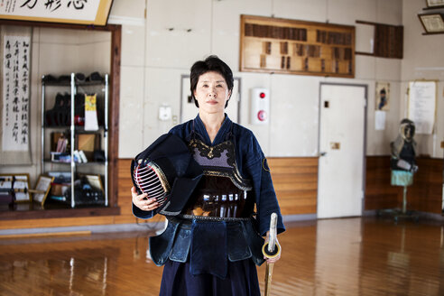 Female Japanese Kendo fighter standing in a gym, holding Kendo mask and sword, looking at camera. - MINF09623