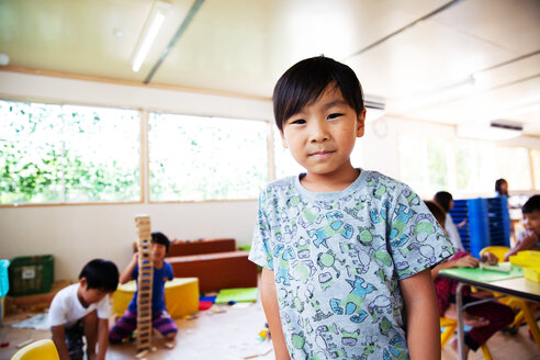 Young boy standing in a classroom in a Japanese preschool, smiling at camera. - MINF09638