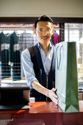 Japanese salesman with moustache wearing glasses standing at counter in clothing store, holding green shopping bag, smiling at camera. - MINF09681