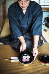 Japanese man wearing traditional kimono knelling on floor, holding a bowl with Wagashi, sweets traditionally served during a Japanese Tea Ceremony. - MINF09684