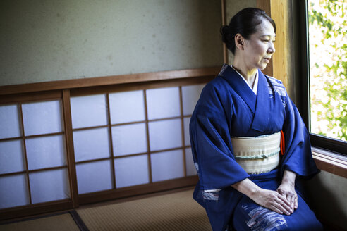 Japanese woman wearing traditional bright blue kimono with cream coloured obi kneeling on floor in traditional Japanese house. - MINF09687