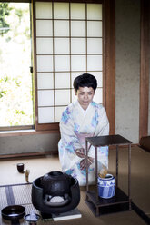 Japanese woman wearing traditional white kimono with blue floral pattern kneeling on tatami mat during tea ceremony. - MINF09690