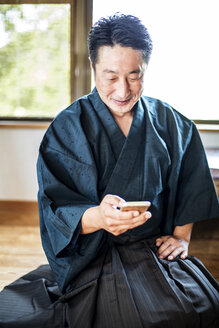 Japanese man wearing kimono sitting on floor in traditional Japanese house, using mobile phone. - MINF09693