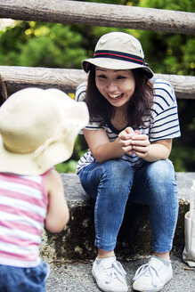 Smiling Japanese woman talking to little girl wearing sun hat, striped top and jeans. - MINF09702