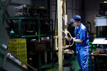 Japanese man wearing baseball cap and blue overall standing in factory, working at a machine. - MINF09705