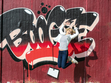 Happy mature woman jumping in the air in front of graffiti wall - LA02169