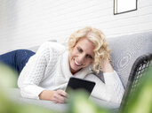 Smiling mature woman lying on couch at home reading e book - LAF02172