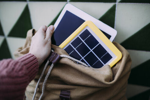 Woman putting a tablet into a backpack with a solar panel charger - GEMF02565