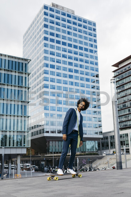 Spain, Barcelona, young businessman riding skateboard in the city - JRFF02036 - Josep Rovirosa/Westend61