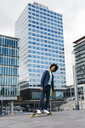 Spain, Barcelona, young businessman riding skateboard in the city - JRFF02036