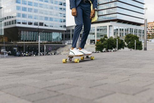 Spain, Barcelona, legs of young businessman riding skateboard in the city - JRFF02039
