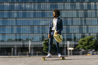 Spain, Barcelona, young businessman riding skateboard in the city - JRFF02042