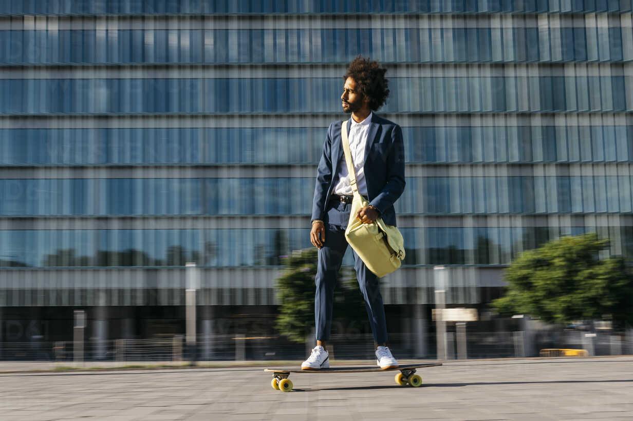 Spain, Barcelona, young businessman riding skateboard in the city - JRFF02042 - Josep Rovirosa/Westend61