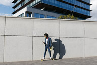Spain, Barcelona, young businessman riding skateboard and using cell phone in the city - JRFF02048