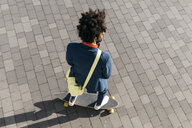Young businessman riding skateboard on a square - JRFF02051
