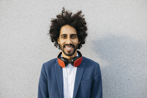 Portrait of smiling young businessman with headphones at a wall - JRFF02057