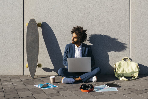 Young businessman sitting outdoors at a wall working on laptop - JRFF02060