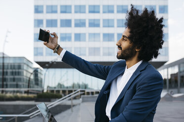Spain, Barcelona, smiling young businessman taking a selfie in the city - JRFF02069
