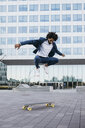 Spain, Barcelona, young businessman doing skateboard tricks in the city - JRFF02078